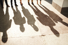Shadows Of Five Businesspeople Standing Outdoors, Bright Sunbeams Illuminating Shabby Asphalt Surface