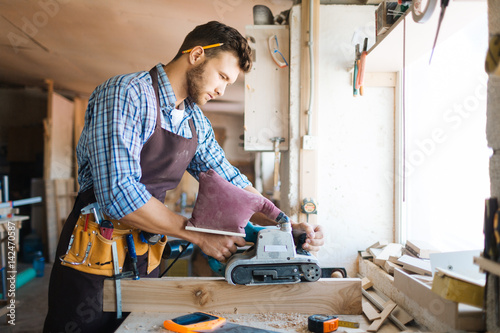 Tableau sur Toile Young bearded carpenter in apron sanding plank in workshop, workbench covered wi