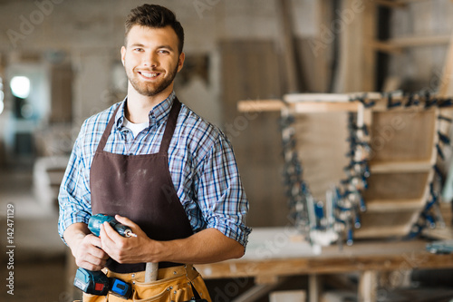 Fotografia Waist-up portrait of smiling bearded craftsman with electric drill in hands stan