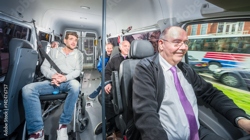 Group of people, travelling in a minivan with a busdriver and disabled person