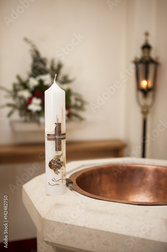 Baptismal candle on font Fototapeta
