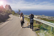 Friends with backpacks are walking along the mountain road