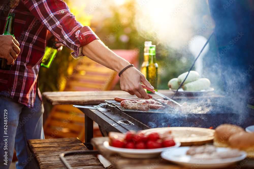 Fototapety, obrazy: Young men roasting barbecue on grill in cottage countryside.