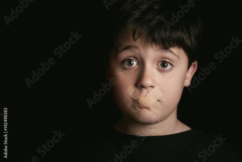 Valokuva niño con tiritas en la boca