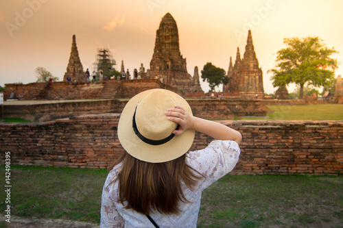Lady tourist is touching her hat and looking at Wat Chaiwatthanaram while sunset in Ayutthaya ancient city.