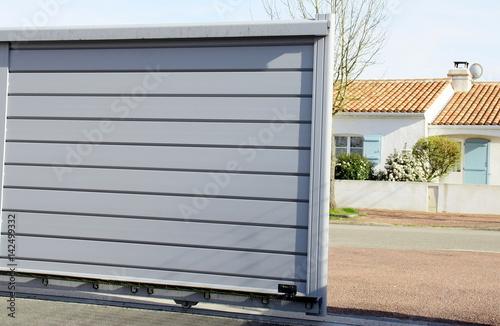 Obraz portail en alu gris ouvert sur maison - fototapety do salonu