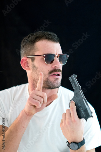 Handsome guy with t-shirt and sunglasses holding a handgun плакат