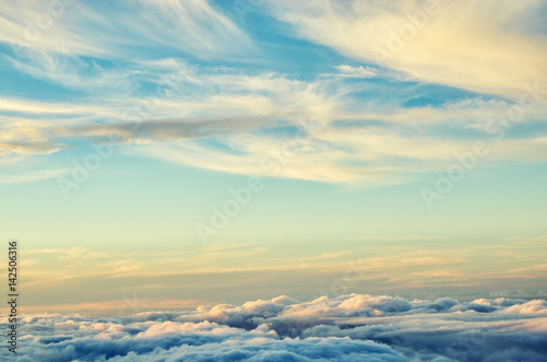 Gold and blue colors clouds abstract background. Sunset sky above the clouds. Universal background in soft pastel colors.