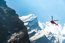 Red Helicopter Flying Near Mountain Peak