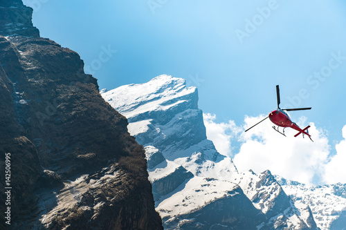 Tuinposter Helicopter Red Helicopter flying near mountain peak