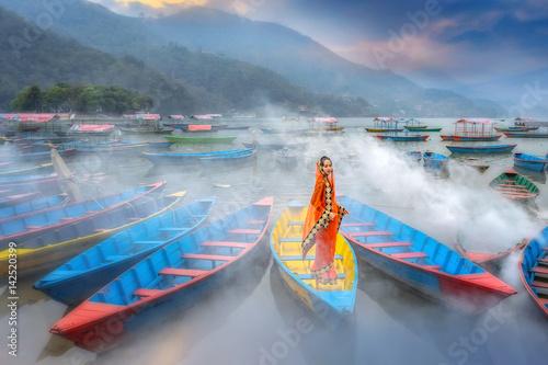 Fotografie, Obraz  Women in sari standing on the boat,Phewa lake,Pokhara city , Nepal