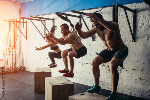 Group of man and woman jumping on fit box at gym Obraz na płótnie