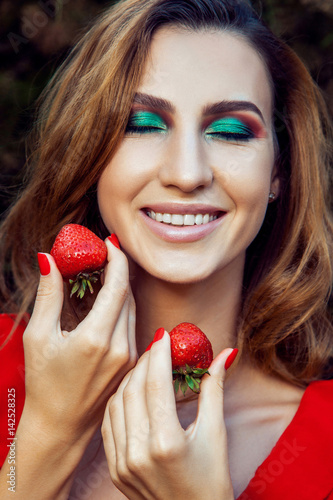 0198cff1ce7f0 Young beautiful happy funny girl with red dress and makeup holding  strawberry in summertime in the park. healthy lifestyle