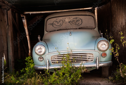 Fotografía Abandoned classic car in overgrown garage with smiling faces drawn in the dusty