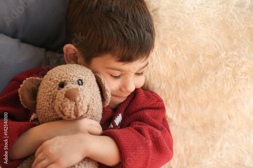 Cute little boy with teddy bear sleeping at home