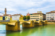 Historical buildings stretched alongside river Arno in the historical center of the italian city Florence.