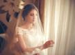 Beautiful bride in white wedding dress standing near the window