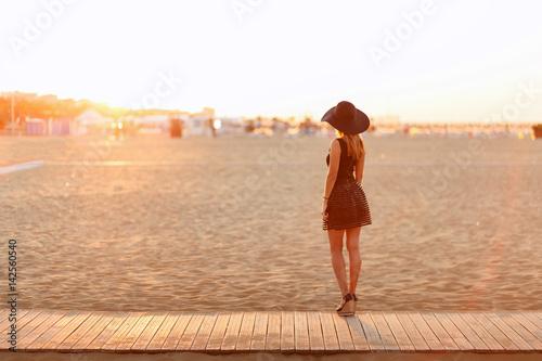 Canvas Print Junge schlanke Frau steht am Strand und schaut auf den Sonnenaufgang