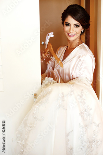 Brunette bride in silk robe stands with wedding dress in her arms ... 321e4f9e8