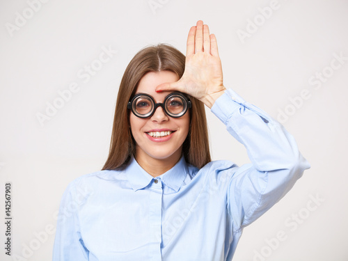 Fotografie, Obraz  Studio portrait of funny happy  young business woman in nerd eyeglasses isolated on gray
