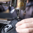 Tailor man sews up a bag in a workshop
