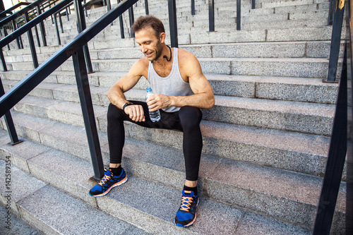 Fototapety, obrazy: Sportsman with bottle of water is resting and checking his smart watch after running. fitness, sport, exercising and people healthy lifestyle concept.