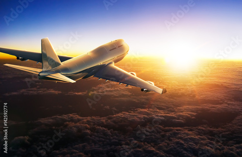 Poster Avion à Moteur Airplane flying above clouds during sunset