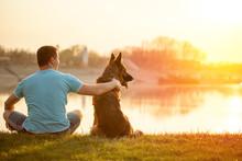 Relaxed Man And Dog Enjoying Summer Sunset Or Sunrise