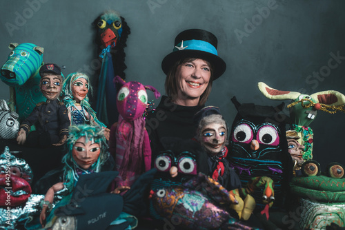 Photo  Smiling puppeteer standing between handmade puppets.