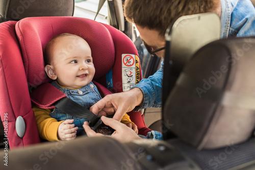 Fotografie, Obraz  Father fasten his baby in car seat