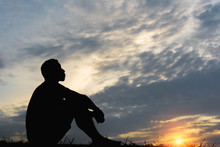 Silhouette Of A Man Sitdown With So Sad In The Sunset.