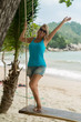 Young blonde woman on swing on a beach