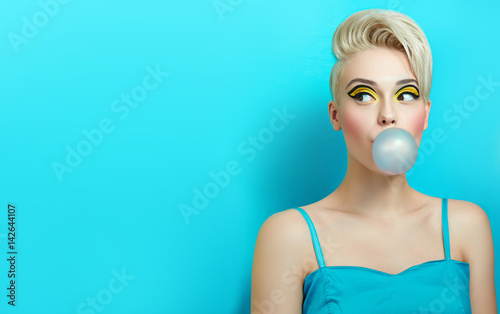 Photo  Fashionable girl with a stylish haircut inflates a chewing gum