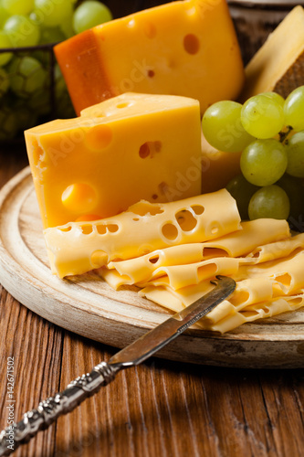 Foto  Mix cheese on wooden board.