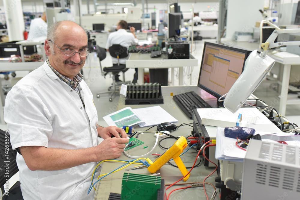 älterer Arbeiter montiert und repariert Elektronik in einer Fabrik ...