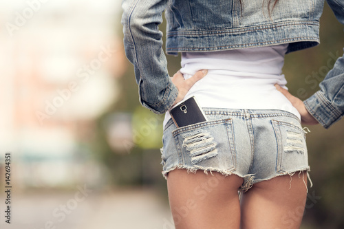 Fotografía  Woman back closeup. Smartphone in jeans short pocket.