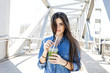 Spain, Barcelona, portrait of smiling young woman with beverage on a bridge