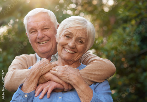 Foto  Happy senior couple smiling contently together outside