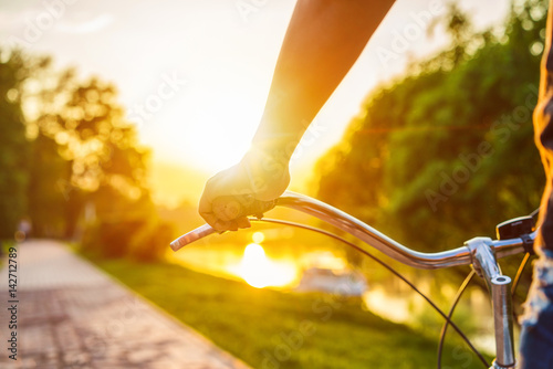 Foto auf AluDibond Fahrrad Hands holding handlebar of a bicycle at the summer sunset.