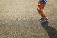 Kid Playing Hopscotch On Playground