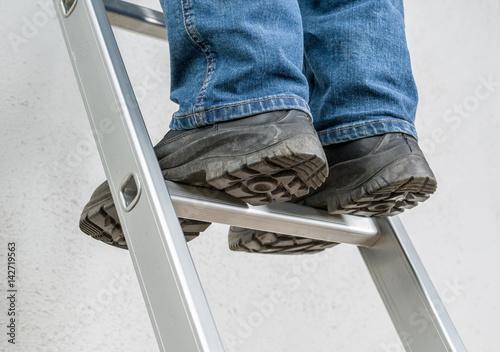Fotografiet  Mann steht auf Leiter