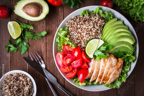 Poster Eten Healthy salad bowl with quinoa, tomatoes, chicken, avocado, lime and mixed greens (lettuce, parsley) on wooden background top view. Food and health.