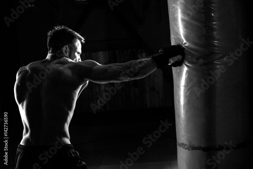Fotografie, Tablou Young male boxer hitting punching bag on black background.