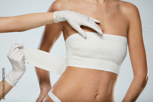 Foto Plastic Surgery. Doctor Hands Wrapping Female Breast In Bandage