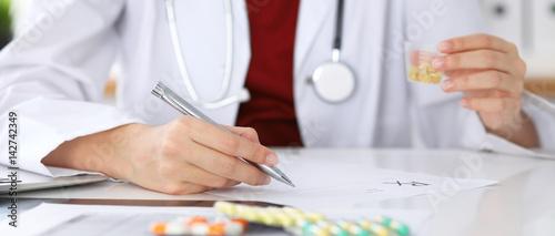 Valokuvatapetti Female medicine doctor fills up  prescription form to patient closeup