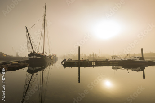 Foto auf AluDibond Pier Fishing boats awaiting delayed departure in harbour due to heavy fog