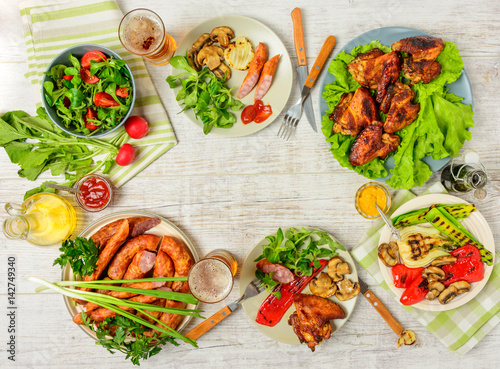 Fototapeta Dinner table with variety food, fried chicken wings, sausages, grilled vegetables in a pan, salad and  lager beer on wooden table. Top view. Copy space. Indoor food Concept. obraz na płótnie