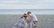Romantic couple kissing on beach cuddling under warm blanket at sunset