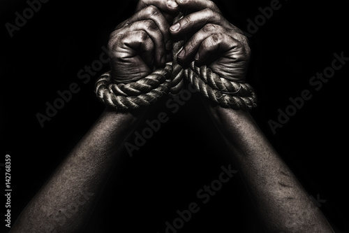 Photo woman hands bound prisoner in room