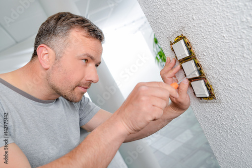 Fotografie, Obraz  Man screwing row of three switches to wall
